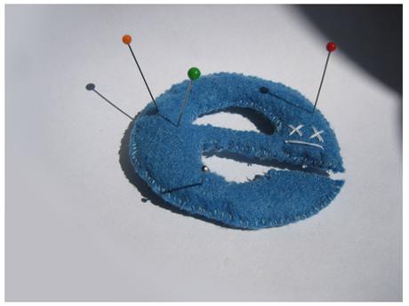 Bambola voodoo a forma di logo di Internet Explorer, trafitta con spilloni.
